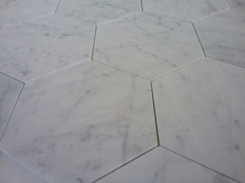 Primo piano del mosaico in marmo Bianco Carrara levigato ad esagoni